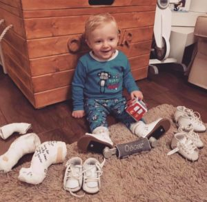 Little boy wearing 'boots and bars' surrounded by old boots and casts